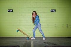 Mujer de pelo largo hermosa con un monopatín de madera cerca de un gree Imagen de archivo