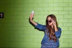 Mujer de pelo largo hermosa con un smartphone cerca de un ladrillo verde Fotografía de archivo