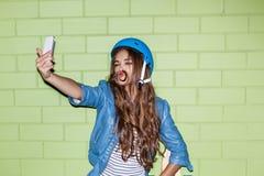 Mujer de pelo largo hermosa con un smartpnone cerca de un ladrillo verde Imagen de archivo