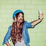 Mujer de pelo largo hermosa con un smartpnone cerca de un ladrillo verde Imagen de archivo libre de regalías