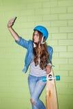 Mujer de pelo largo hermosa con un smartpnone cerca de un ladrillo verde Fotos de archivo libres de regalías