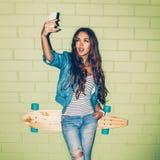 Mujer de pelo largo hermosa con un teléfono móvil cerca de un ladrillo verde Imágenes de archivo libres de regalías