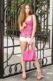 Mujer de pelo largo hermosa en un estilo atractivo rosado transparente de la ropa que camina abajo de la calle Foto de archivo