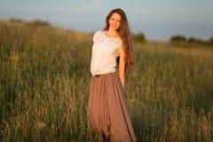 Mujer de pelo largo hermosa en una falda y una blusa blanca Fotos de archivo libres de regalías