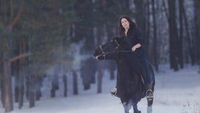 Mujer de pelo largo hermosa que monta un caballo negro a través de la nieve en el bosque, el encabritarse del semental foto de archivo