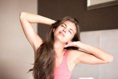 Mujer de pelo largo joven feliz hermosa que despierta imagen de archivo