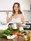 Mujer de pelo largo ordinaria que cocina la sopa Foto de archivo libre de regalías