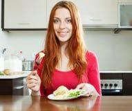 Mujer de pelo largo que come las patatas en casa Fotografía de archivo