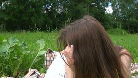 Mujer de pelo oscuro bonita joven que miente en la hierba en un parque almacen de video