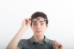 Mujer de pelo oscuro hermosa joven en camisa gris con miradas del asombro hacia arriba, contra el fondo blanco del estudio Fotografía de archivo
