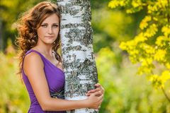 Mujer de pelo oscuro linda cerca del árbol de abedul Imagen de archivo