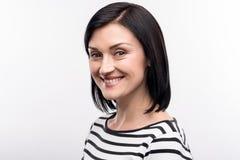 Mujer de pelo oscuro optimista que presenta para la cámara Imagen de archivo libre de regalías