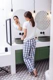 Mujer de pelo oscuro que lleva los pantalones ajustados del pijama que quitan maquillaje imagen de archivo