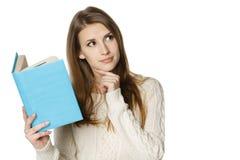 Mujer de pensamiento con el libro abierto que mira a la cara Imágenes de archivo libres de regalías