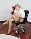 Mujer de pensamiento de los busienss que se sostiene principal en guante de boxeo Foto de archivo libre de regalías