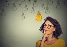 Mujer de pensamiento en los vidrios que miran para arriba con el bulbo ligero de la idea sobre la cabeza Imágenes de archivo libres de regalías