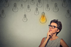 Mujer de pensamiento en los vidrios que miran para arriba con el bulbo ligero de la idea sobre la cabeza Fotografía de archivo