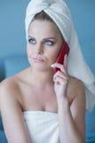 Mujer de pensamiento en toalla de baño con el teléfono celular rojo Imagenes de archivo