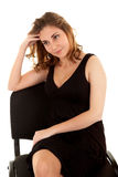 Mujer de pensamiento en una alineada negra en una silla fotos de archivo libres de regalías