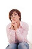 Mujer de pensamiento que mira para arriba con la mano en la barbilla Fotos de archivo