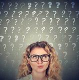 Mujer de pensamiento que mira para arriba muchos signos de interrogaciones sobre la cabeza fotos de archivo