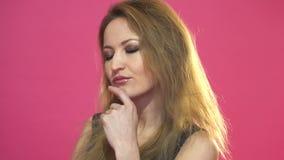 Mujer de pensamiento que mira para arriba y alrededor el copyspace Modelo femenino en fondo rosado almacen de video