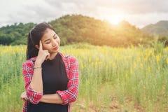 Mujer de pensamiento que se coloca en el campo de flor Imagen de archivo