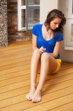 Mujer de pensamiento que se sienta en el piso Imagen de archivo