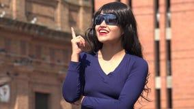 Mujer de pensamiento que tiene gafas de sol que llevan y peluca de una idea almacen de metraje de vídeo