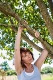 Mujer de pensamiento 50s debajo de un árbol para la metáfora de la paz Imagen de archivo libre de regalías
