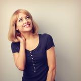 Mujer de pensamiento sonriente dentuda de risa que mira para arriba en espacio vacío Foto de archivo