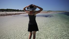 Mujer de pie en la playa almacen de video