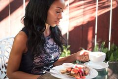 Mujer de piel morena elegante que desayuna en la terraza de a Fotos de archivo libres de regalías