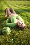 Mujer de Pregnantt en hierba con el melón Imagenes de archivo
