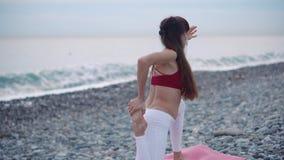 Mujer de relajación que hace yoga en la playa almacen de metraje de vídeo