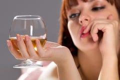 Mujer de relajación soñadora con el vidrio de vino Imagen de archivo libre de regalías