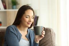 Mujer de Relaxd que goza de una taza de café en un sofá fotos de archivo libres de regalías