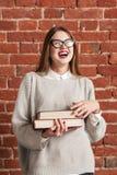 Mujer de risa atractiva con el retrato de los libros Imagenes de archivo
