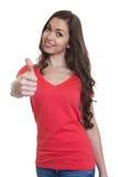 Mujer de risa con el pelo oscuro largo y la camisa roja que muestran el pulgar Foto de archivo libre de regalías
