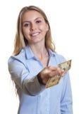 Mujer de risa con el pelo rubio largo que da el dólar  Foto de archivo libre de regalías