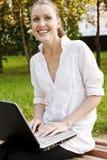 Mujer de risa con la computadora portátil Imagen de archivo libre de regalías