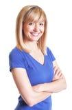 Mujer de risa con los ojos oscuros y los brazos cruzados en una camisa azul Fotografía de archivo libre de regalías