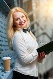 Mujer de risa del jengibre con los labios rojos que sostienen el cuaderno Fotografía de archivo