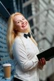 Mujer de risa del jengibre en la camisa blanca que sostiene el cuaderno Fotografía de archivo libre de regalías