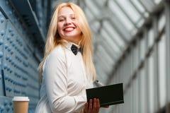 Mujer de risa del jengibre que sostiene el cuaderno en pasillo largo Fotografía de archivo
