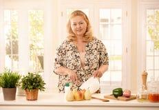 Mujer de risa en cocina Imagenes de archivo