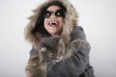 Mujer de risa en el abrigo de pieles encapuchado que sostiene el gato Imagen de archivo