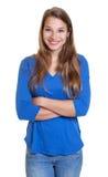 Mujer de risa en una camisa azul con los brazos cruzados Imagen de archivo libre de regalías