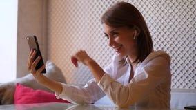 Mujer de risa feliz hacer la llamada video usando el teléfono móvil almacen de video