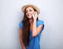 Mujer de risa hermosa en sombrero del verano que habla en el teléfono móvil o Imagen de archivo libre de regalías